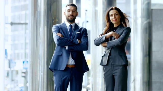 Male and Female Business People Cross Arms and Smile While Standing in the Middle of the Central Business District Street. video