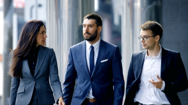 male and female business people walk and discuss business. they're all working in central business district. - professione finanziaria video stock e b–roll