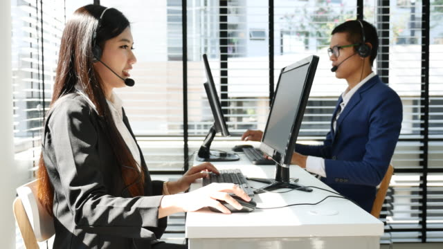 Male and female call center workers wearing headsets Male and female call center workers wearing headsets call centre videos stock videos & royalty-free footage