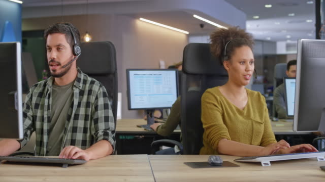 DS Male and female call centre agent providing customer service at their working stations Medium dolly shot of a male and female call centre agent providing customer service at their working stations in a modern office. Shot in Slovenia. call center stock videos & royalty-free footage