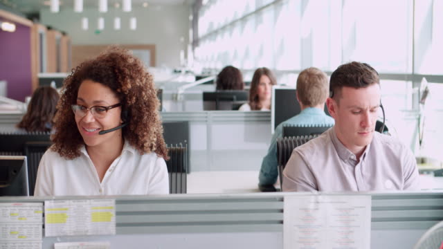 Male and female call centre workers wearing headsets Male and female call centre workers wearing headsets call centre videos stock videos & royalty-free footage