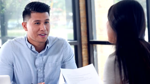 Male and female colleagues review document together Young Asian businessman hands a document to a female colleague or coworker. The two business colleagues discuss the document together. interview event stock videos & royalty-free footage