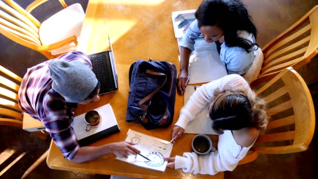 Male and female college students study for exam in coffee shop Group of college students or young business professionals review charts and graphs while in a trendy coffee shop. After reviewing a chart, a young man uses a laptop. They then continue to examine the chart. university student stock videos & royalty-free footage