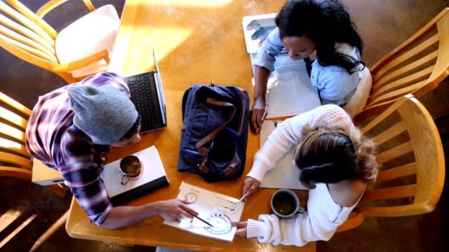 männliche und weibliche college-studenten studieren für prüfung in coffeeshop - akademisches lernen stock-videos und b-roll-filmmaterial