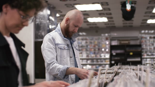 Video Male and Female Customers Looking through Vinyl Discs in Record Store