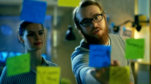 male and female designers plan their next project on a glass wall with sticky notes outline. they're young and creative people who work in a stylish loft space. - post it video stock e b–roll
