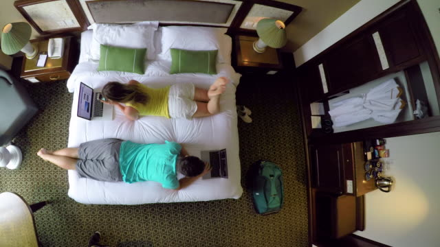 TOP DOWN: Male and female digital nomads working on computers from hotel room.