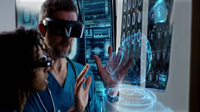 Male and female doctor examining brain scan Medium close-up of a male and a female doctor examining 3D brain hologram while wearing VR headsets hologram stock videos & royalty-free footage