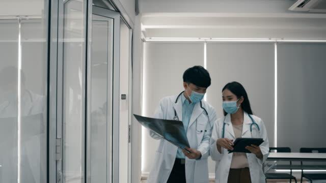 man och kvinna läkare gå igenom på sjukhus - corona vaccine bildbanksvideor och videomaterial från bakom kulisserna
