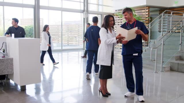 男、女醫生在醫院大堂談話 - surgeon 個影片檔及 b 捲影像
