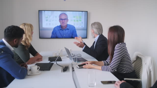 Male and Female Executive Team Video Conferencing with CEO Mid distance personal perspective of CEO holding video conference with male and female executive team. ceo stock videos & royalty-free footage