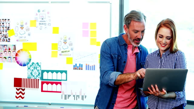 männliche und weibliche führungskräfte diskutieren über laptop - reliability stock-videos und b-roll-filmmaterial