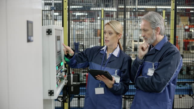 Male and female factory employee talking about the values shown on the machine's LCD screen Wide handheld shot of a male and female factory worker discussing the values shown on the tablet the woman is holding and comparing them to the ones shown on the machine's LCD screen. Shot in Slovenia. manufacturing occupation stock videos & royalty-free footage