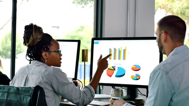 männliche und weibliche finanzanalysten überprüfen finanzcharts - geschäftsstrategie stock-videos und b-roll-filmmaterial