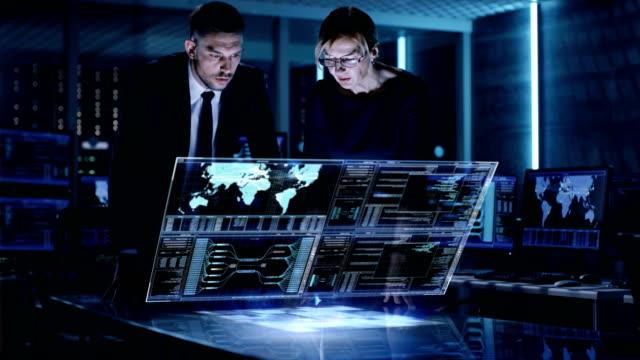 männliche und weibliche regierung agenten verwendung touchscreen interaktive 3d panel bei der überwachung der großen raum voller computer mit animierten screens. - holografisch stock-videos und b-roll-filmmaterial