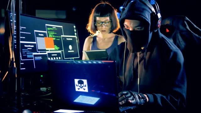 男性と女性のハッカーはコンピューター室で一緒に作業をしています。 - なりすまし犯罪点の映像素材/bロール