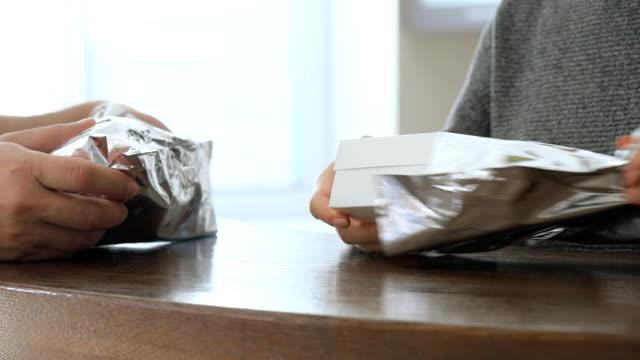 남성과 여성의 손에 햄버거와 골 판지 상자를 엽니다. - burger and chicken 스톡 비디오 및 b-롤 화면