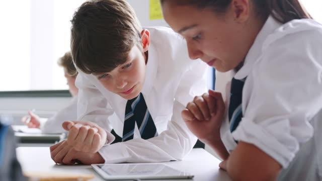 デジタルで統一作業を着ている男性と女性の高校生が一緒にデスクでタブレットします。 - 制服点の映像素材/bロール