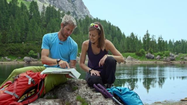 Macho y hembra excursionista comprobando el mapa sentado en el lago alto en las montañas - vídeo