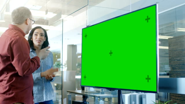 male and female  in conference room have discussion about mock-up chroma key green screen tv. - electronics stock videos and b-roll footage