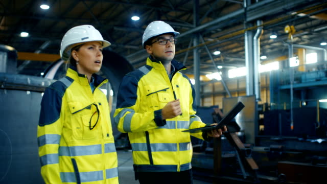 Male and Female Industrial Engineers in Hard Hats and Safety Jackets Discuss New Project while Using Laptop. They Walk Through on a Heavy Industry Manufacturing Factory with Metalwork Components Lying Around.