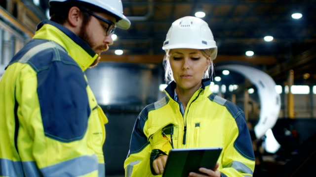 Male and Female Industrial Engineers in Hard Hats and Safety Jackets Discuss New Project while Using Tablet Computer. They Work at the Heavy Industry Manufacturing Factory.