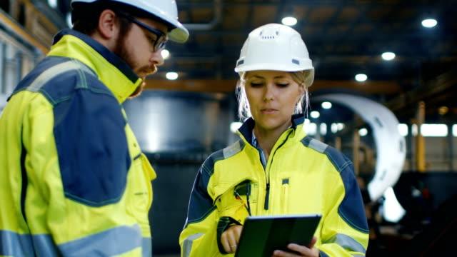 männliche und weibliche wirtschaftsingenieure in harte hüte und jacken diskutieren neue projekt sicherheit beim tablet-computer verwenden. sie arbeiten in der schwerindustrie manufacturing factory. - bauarbeiterhelm stock-videos und b-roll-filmmaterial
