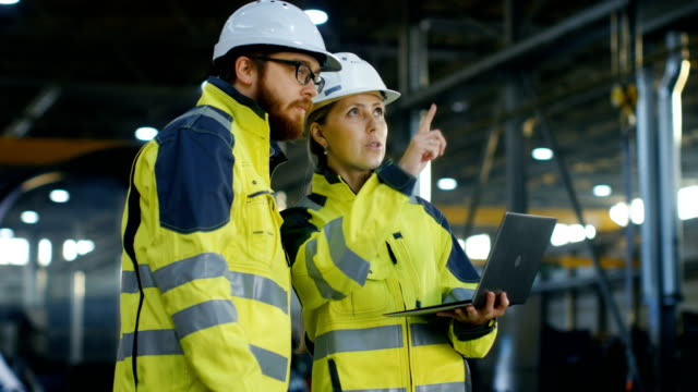 male and female industrial engineers in hard hats discuss new project while using laptop. they make showing gestures.they work at the heavy industry manufacturing factory. long shot. - bezpieczeństwo filmów i materiałów b-roll