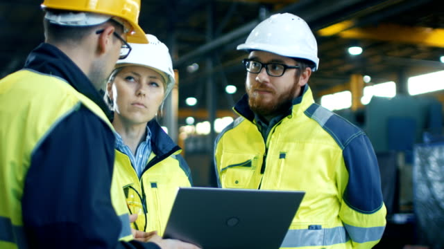 male and female industrial engineers talk with factory worker while using laptop. they work at the heavy industry manufacturing facility. - collaboration stock videos & royalty-free footage