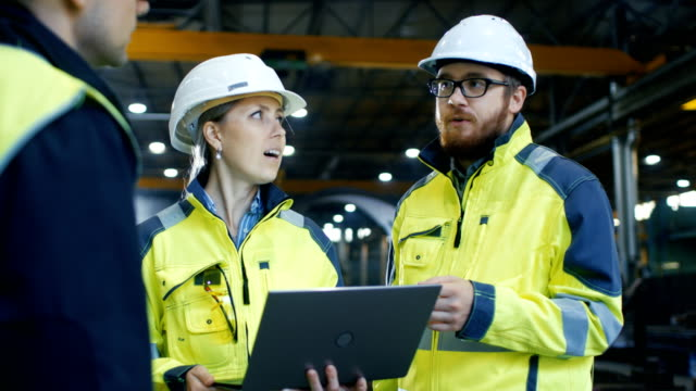 male and female industrial engineers talk with factory worker while using laptop. they work at the heavy industry manufacturing facility. - metallurgia video stock e b–roll