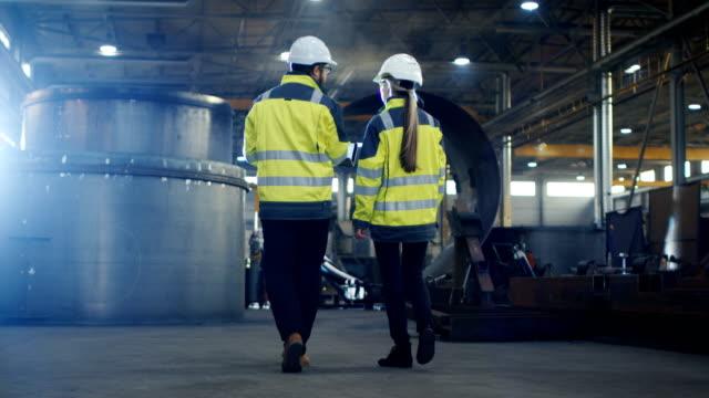 männliche und weibliche wirtschaftsingenieure verwendung laptop und haben diskussion während zu fuß durch schwerindustrie manufacturing factory. sie tragen hart hüte und sicherheitswesten. - bauarbeiterhelm stock-videos und b-roll-filmmaterial