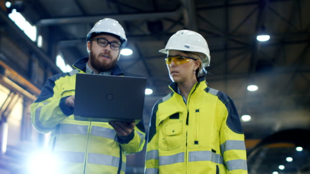 male and female industrial engineers use laptop and have discussion while walking through heavy industry manufacturing factory. they wear hard hats and safety jackets. - тяжёлый стоковые видео и кадры b-roll