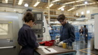 istock Male and female industrial laborers at their work station in a water pump factory 1206324792