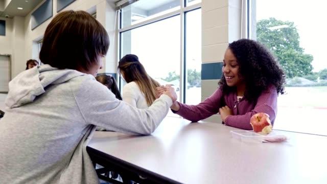 vídeos y material grabado en eventos de stock de los estudiantes de secundaria masculinos y femeninos luchan por el brazo durante el almuerzo - escuela media
