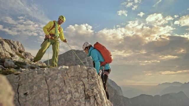 vídeos de stock, filmes e b-roll de masculina e feminina alpinista a subir para o topo da montanha com ajuda do alpinista no topo - eslovênia