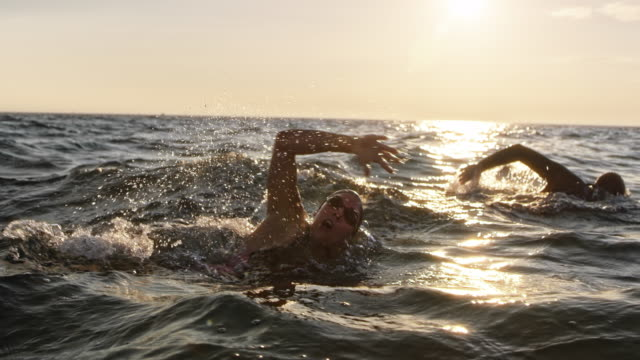 SLO MO Male and female open water swimmer swimming front crawl at sea in sunshine