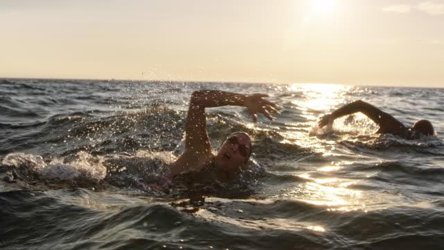 vídeos de stock e filmes b-roll de slo mo male and female open water swimmer swimming front crawl at sea in sunshine - swim arms