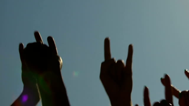 male and female raising hands up, waving to music at open space rock concert - mano donna dita unite video stock e b–roll