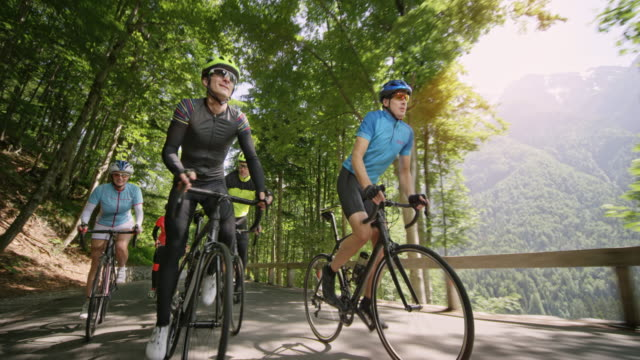 Male and female road cyclists riding on a nice asphalt road in sunshine Wide low angle handheld front shot of male and female road cyclists riding on a nice mountain road on a sunny day. Shot in Slovenia. 30 39 years stock videos & royalty-free footage
