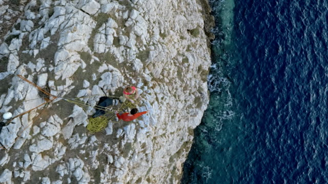 AERIAL Male and female rock climber giving each other a hug as they reach the top of the steep cliff above the sea