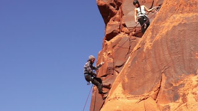 male and female rock climbers in moab - imbracatura video stock e b–roll