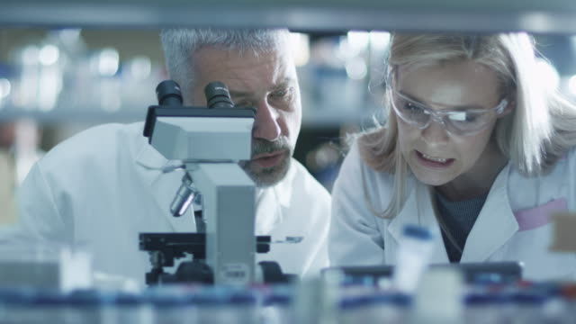 Male and female scientist are working with a microscope and a tablet in a laboratory.