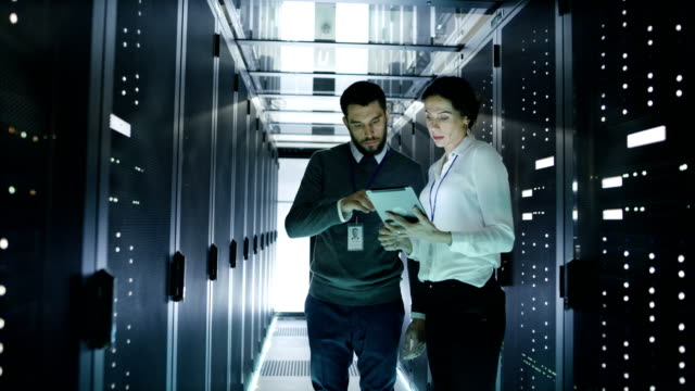 Male and Female Server Technicians Working in Data Center. Running Rack Server Diagnostics. Woman Uses Tablet Computer. video