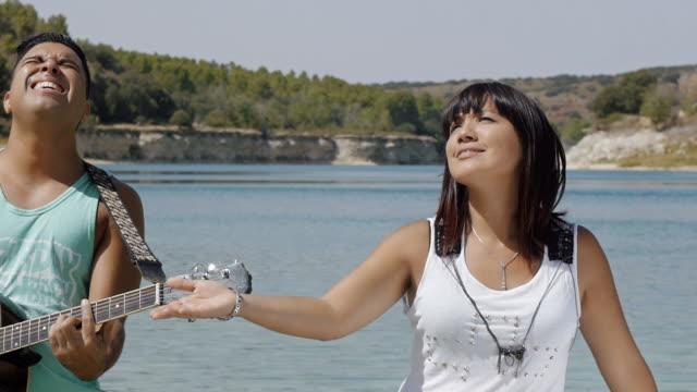manliga och kvinnliga sångare sjunga en låt med en gitarr - akustisk gitarr bildbanksvideor och videomaterial från bakom kulisserna