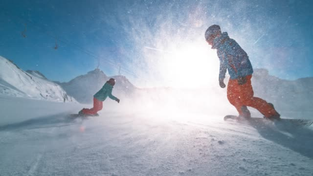 slo mo ts male and female snowboarder riding down a sunny slope and snow particles flying in the air - snowboarding video stock e b–roll