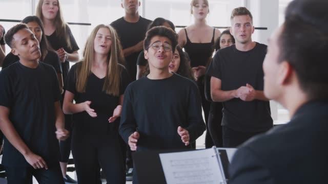 erkek ve kadın öğrenciler sinema okulu 'nda öğretmen ile koro singing - orta plan plan türleri stok videoları ve detay görüntü çekimi