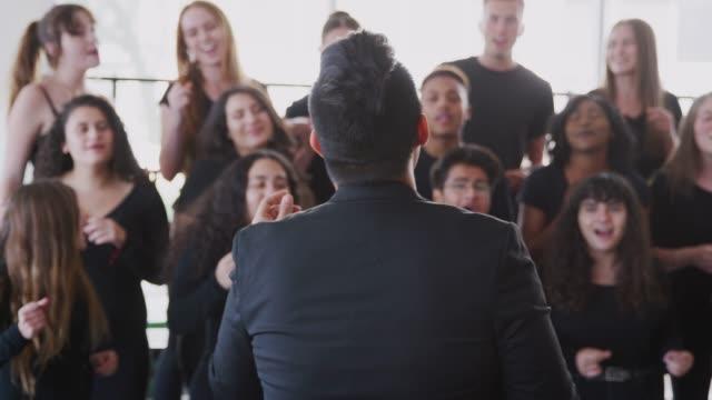 manliga och kvinnliga studenter sjunger i kören med lärare på performing arts school - sångare artist bildbanksvideor och videomaterial från bakom kulisserna