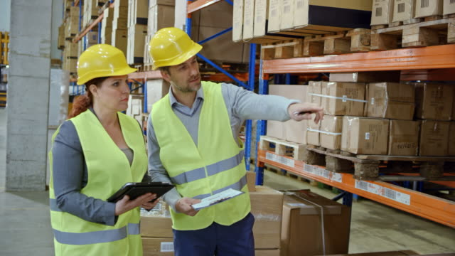 Male and female supervisors checking the inventory in the warehouse video