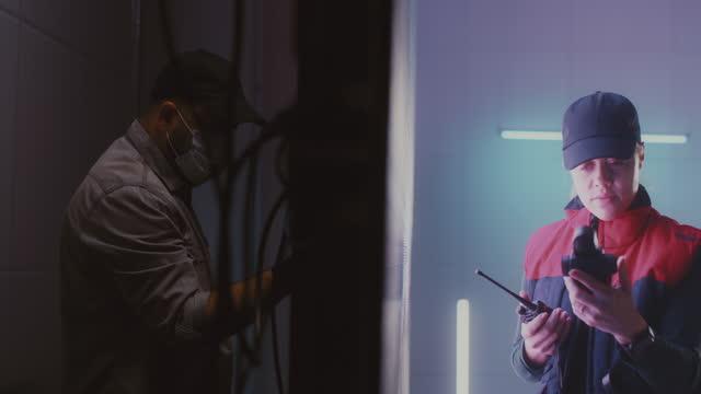 мужчины и женщины техников проводки светодиодный экран вместе - covid testing стоковые видео и кадры b-roll