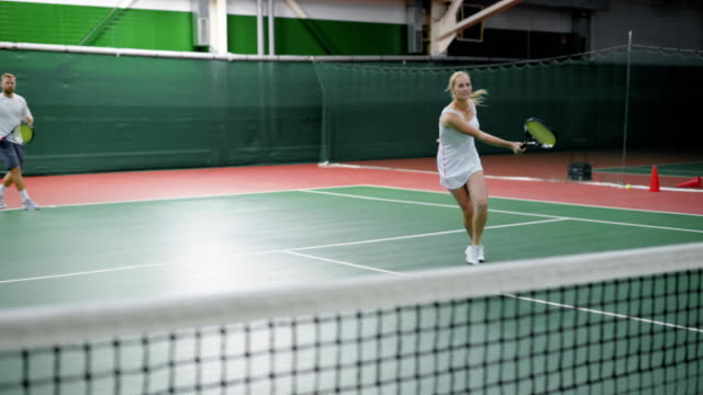Male and female tennis team playing match on court video